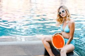 Fotografie beautiful girl in swimsuit posing with watermelon at poolside