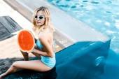 krásná dívka v plavkách a sluneční brýle pózuje s meloun v bazénu