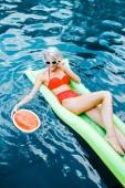 mosolygó, szőke nő fürdőruha pihentető medence görögdinnye-zöld felfújható matrac