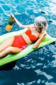 Fotografia ragazza bionda in costume da bagno che si trova sul materasso gonfiabile verde in piscina con ananas: Pinup