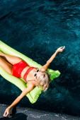 Fotografie pohled shora PIN se dívka v plavkách relaxační na zelené nafukovací matraci v bazénu