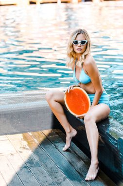 attractive blonde girl in swimsuit posing with watermelon at poolside