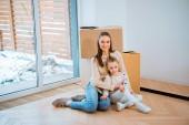 Fényképek vidám anya átfogó aranyos lánya emeleten új otthon ülve