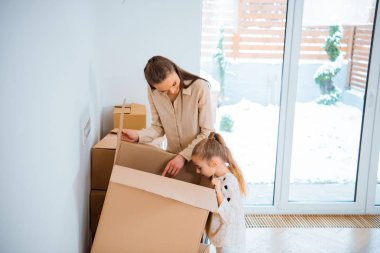 Happy mother standing near cute daughter looking inside box in new home stock vector