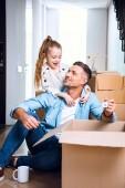 Fotografia allegra figlia guardando padre con portachiavi a forma di casa che si siede sul pavimento