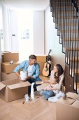 Photo happy family sitting on floor near boxes in new home