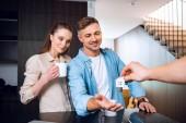 oříznutý pohled člověka dávat dům ve tvaru přívěšek na klíče k šťastnému páru v novém domově