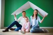 glückliches Ehepaar hält Papierdach, während es neben Tochter auf dem Boden sitzt