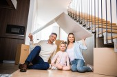 Photo happy family sitting under paper roof and smiling in new home