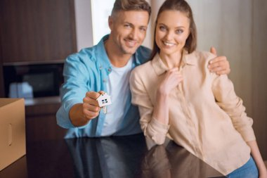 selective focus of house shaped key chain in hand of handsome man hugging wife