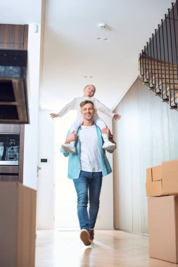 happy father carrying on neck cheerful daughter in new home