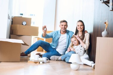 happy man sitting on floor with house shaped key chain near attractive wife and daughter