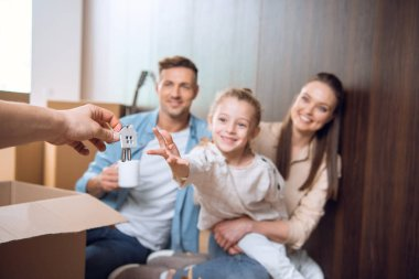 selective focus of house shaped key chain with smiling kid sitting near parents on background