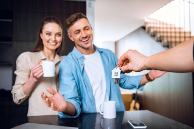 selective focus of man giving house shaped key chain to happy couple in new home
