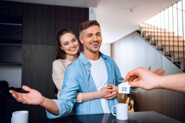 cropped view of man giving house shaped key chain to cheerful couple in new home