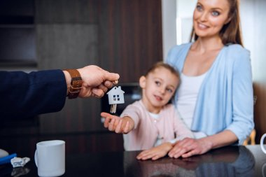 selective focus of broker giving house shaped key chain to cheerful mom and daughter