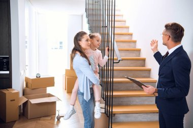 handsome broker showing stairs to attractive woman holding in arms cute daughter