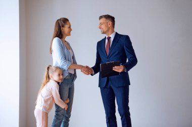 handsome broker shaking hands with attractive woman standing with cute daughter