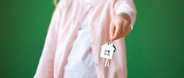 cropped view of kid holding house shaped key chain isolated on green
