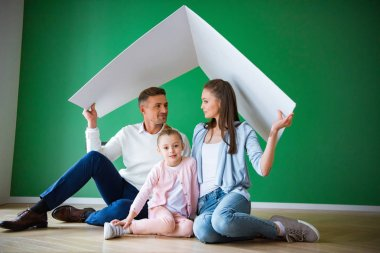 Happy husband and wife looking at each other near cute daughter and holding paper roof while sitting on floor stock vector