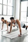 Fotografie sportovní mladý pár v sportovní dělá push up na jógu v tělocvičně