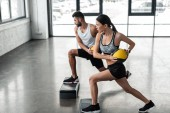 Fotografie Seitenansicht des sportlichen jungen Paar Betrieb Medizinbälle und auf Schritt-Plattformen im Fitness-Studio trainieren