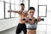 Selektivní fokus sportovní mladý pár tréninku s činkami v posilovně