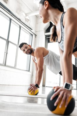 athletic young couple smiling each other while exercising with medicine balls on yoga mats in gym