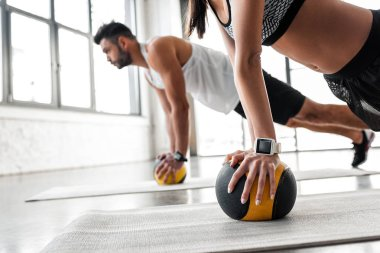 cropped shot of young sportive couple exercising with medicine balls on yoga mats