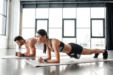 side view of athletic young couple in sportswear doing plank exercise on yoga mats in gym