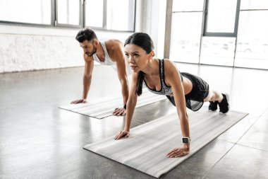 sportive young couple doing push ups on yoga mats in gym