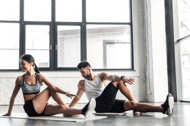 athletic young couple sitting on yoga mats and stretching in gym