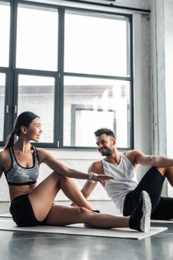 smiling sporty young couple training on yoga mats in gym