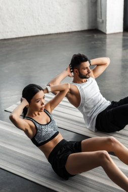 high angle view of young couple doing abs exercise on yoga mats in gym