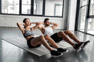 athletic young couple doing abs exercise on yoga mats in gym