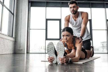 trainer exercising with young sporty woman stretching on yoga mat in gym