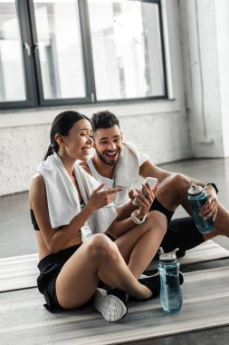 Happy sporty young couple using smartphone together on yoga mats in gym stock vector