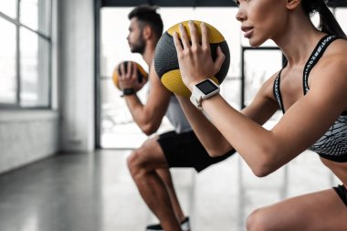 cropped shot of sporty young couple holding medicine balls and training together in gym