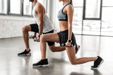 cropped shot of sporty young couple exercising with dumbbells in gym