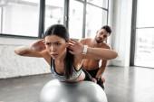 krásná mladá sportovkyně cvičení na fitness míč a košili svalnatý muž za trénink v tělocvičně