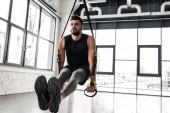 Fotografie gut aussehend muskulösen jungen Sportler mit Federung Riemen im Fitness-Studio trainieren