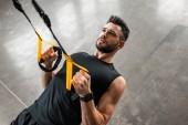 Fotografie erhöhte Ansicht athletischen jungen Mannes in Sportbekleidung hängen und Training mit Widerstand Bands im Fitness-Studio