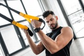 Photo handsome muscular young man looking at biceps while training with suspension straps in gym