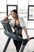 müde junge Sportlerin mit Handtuch stehen auf Laufband und wegschauen im Fitness-Studio