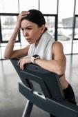 Erschöpfte junge Sportlerin lehnt nach dem Training am Laufband und schaut im Fitnessstudio weg