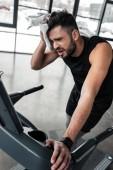 Fotografie müde junge Sportler training auf Laufband und Schweiß mit Tuch abwischen, im Fitness-Studio