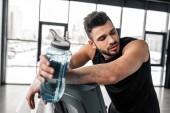 müde junge Sportler an Laufband gelehnt und hält Sport-Flasche mit Wasser im Fitness-Studio