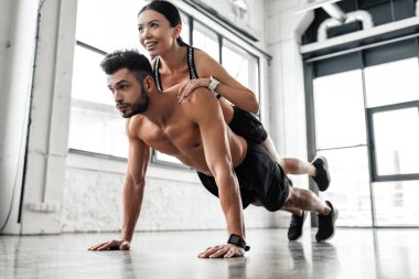 muscular shirtless young man doing push ups with smiling sporty girl on back in gym