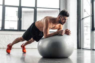 muscular shirtless young man doing plank exercise on fitness ball at gym