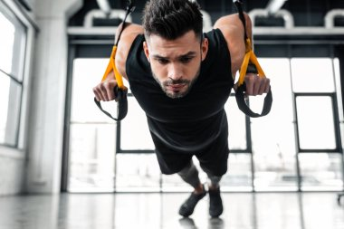 focused muscular young sportsman exercising with suspension straps in gym